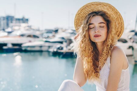 curly blonde with a restrained smile closing her eyes straightens her hat on the background of the pier