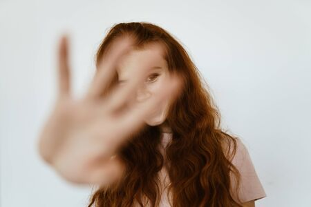 cheerfully smiling red-haired disheveled girl closes the camera with a palm with spread fingers