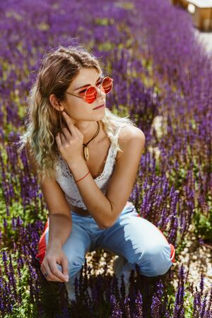 blonde with sportswear squatted among sage flowers and adjusts the earphone in her ear looking into the distance through pink glasses Stockfoto