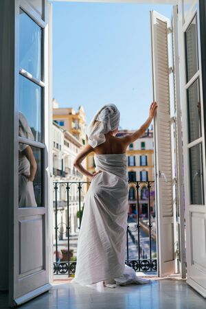 being in self-isolation, the girl went to the balcony, wrapping the body with a sheet and hair with a towel and looking at the street Stok Fotoğraf - 147976562