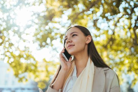 business woman on the background of a tree with autumn leaves speaks on the phone, an expression of serenity on her face
