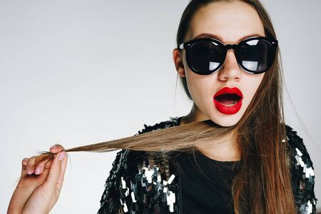 brunette with bright red lipstick on her lips in black glasses, opening her mouth in surprise, wraps a strand of her long hair around her neck Stockfoto