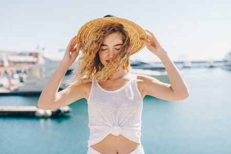 curly blonde head down from the wind holds her hat against the background of the sea and ships Stockfoto