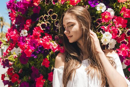 the girl with closed eyes leaned her head against blooming petunias and enjoys their aroma Stockfoto
