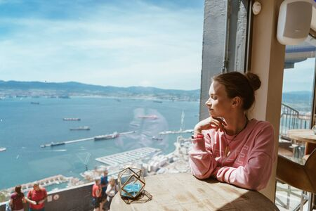nice girl sits by the window in a cafe and looks at the Gibraaltarsky Strait