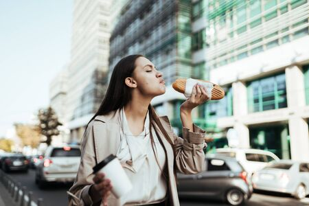 in the business center, a girl eagerly eats a bun with coffee moving along the road with a car