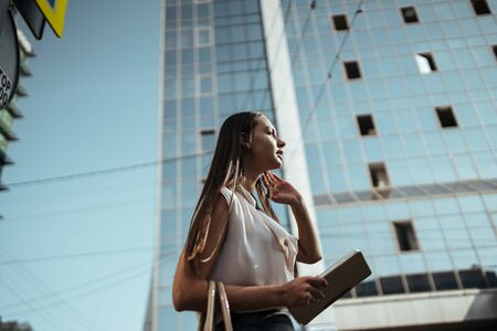 against the background of a glass high-rise building is a girl with a tablet pc in her hands