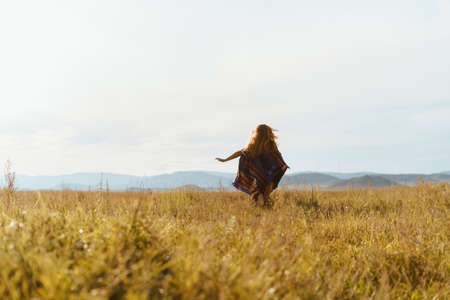 steppe and hills in the distance girl running away with her hands placed on the sides in a poncho on her shoulders, the wind inflates her hair. High quality photo Banco de Imagens