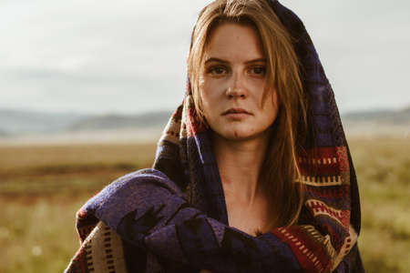 close-up. In the steppe stands a girl without makeup with natural beauty in an ethno cape with strictly looking into the distance. High quality photo