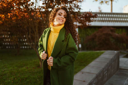 flirtatiously tilting her head and gazing over her shoulder the girl holds her coat and poses in the park. High quality photo