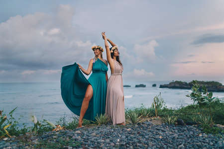Against the background of the ocean two girls in long dresses with wreaths of flowers on the head pose pose. High quality photo