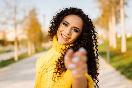 In a yellow bright sweater, a girl with dark curls happily pulls her hands forward. High quality photo Banco de Imagens