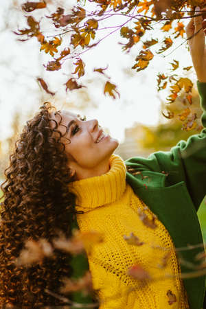 The girl in profile smiles tenderly and looks at the yellow leaves of the tree. High quality photo Banco de Imagens