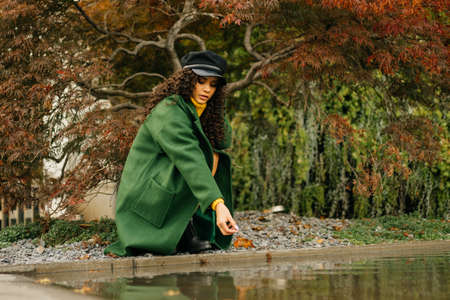 Under the tree with purple leaves at the backwater crouched a girl in autumn clothes and lets into the water autumn leaves. High quality photo Banco de Imagens