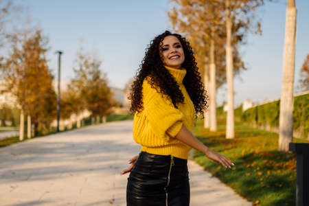 yellow leaves of the park and harmonizing with them yellow sweater dark-haired curly beauty walking on the parks path. High quality photo Banco de Imagens