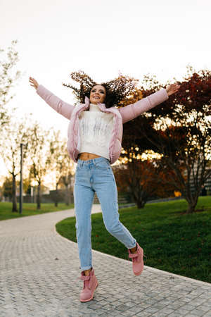 A girl in warm clothes jumps up on the park track, her hair is scattered on the sides and she smiles up her arms. High quality photo