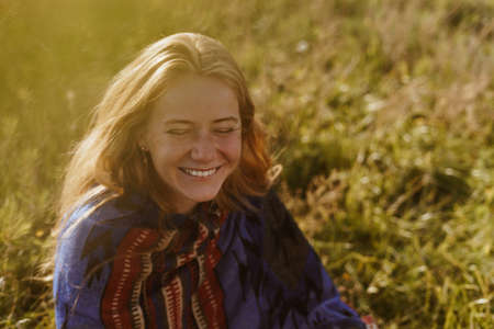 unbridled and cheerfully laughs a girl of natural beauty in an ethno cape sitting in a field on the grass. High quality photo