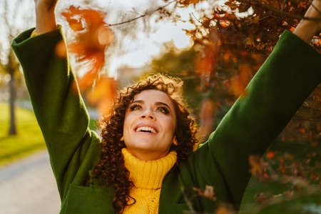 the girl victoriously threw up her arms and looked into the sky gleefully smiling standing under the branches of the autumn tree. High quality photo Stock fotó