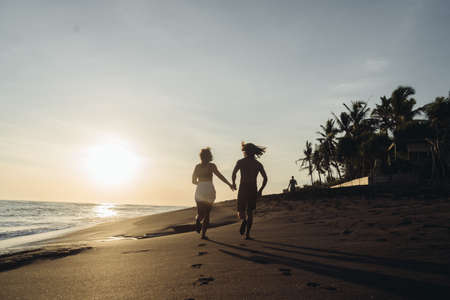 Against the background of sunset over the ocean on the coastal sand run holding hands a man and a woman. High quality photo Imagens