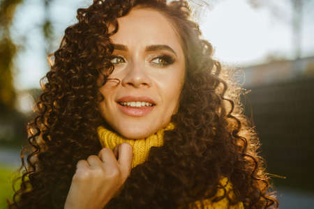 turning over her shoulder with a smile looking into the distance with green eyes looking curly brunette close-up. High quality photo