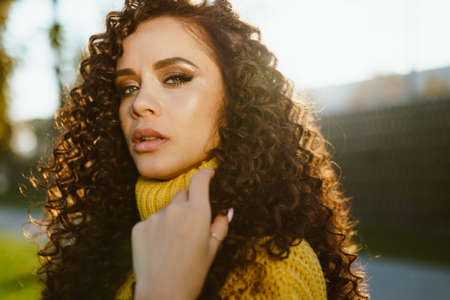 The curly brunette looked chiseled with chiseled facial features inquiringly looking into the camera. close-up. High quality photo
