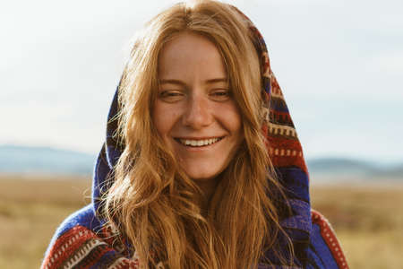 girl with wheat-colored hair in a striped thick scarf sl over her head and shoulders smiling stands in the steppe. High quality photo