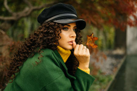 The brooding girl with long curly hair looks in the distance with beautiful eyes the color of her green coat. High quality photo Imagens