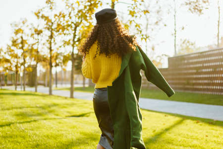 On the park grass is removed from the camera girl with long curly hair in a cap with a coat thrown over one shoulder. High quality photo