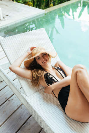 A top view of the girl lying on the schizong by the pool in a hat and swimsuit. High quality photo Stock Photo