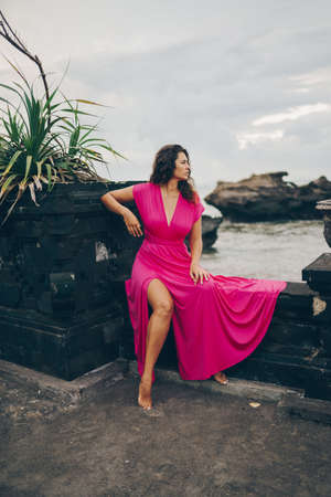 In a pink dress with a cut girl sitting on the embankment looking at the water. High quality photo