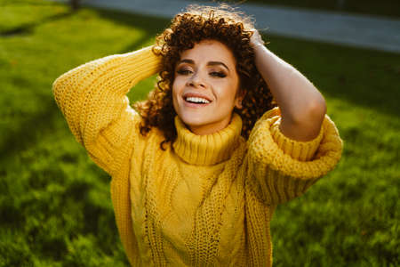 The curly brunette shaggy with her thick hair and smiles cutely against a backdrop of green grass. High quality photo