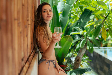 at the wooden wall with a glass in hand stands a beautiful girl in a swimsuit in a distance pool and palm trees. High quality photo
