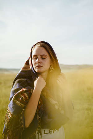 In the field a beautiful girl in an ethno cape on her head covering her eyes set her face to the sun and holds the cape with her hand. High quality photo