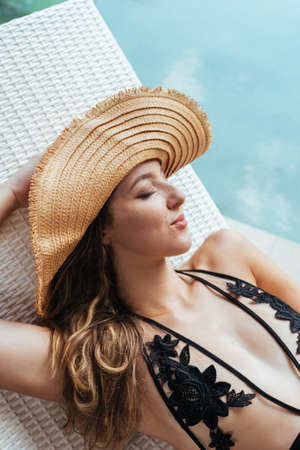 Pool girl in hat from the sun covering her eyes takes sunbathing. High quality photo