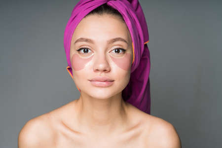 Girl with bare shoulders and towel on her head does spa procedure by sticking pink patches under her eyes. High quality photo Stock Photo