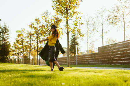 In the park on the green grass comes a girl in a bright sweater throwing on one shoulder coat. High quality photo