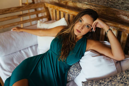 among the pillows on the bed lies a girl propped up her hand head in a long dress. High quality photo Stock Photo