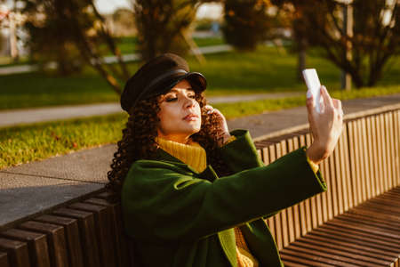 On a wooden bench in the park sits a beautiful brunette with curly hair in a dark green coat and cap and makes selfies. High quality photo