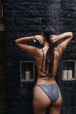 View from the back. Against the background of the brick wall takes a shower slender beautiful girl with long hair and a beautiful figure. High quality photo