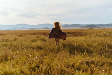 in the distance runs across the field with fluttering hair and a cape barefoot girl. High quality photo Stock Photo