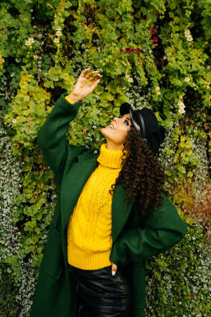 Against the background of green ivy stands a beautiful girl in a bright yellow sweater with curly thick dark hair. High quality photo