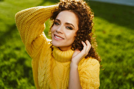 Against the background of green grass green-eyed brunette collects in a bun her luxurious hair and charmingly smiles. High quality photo