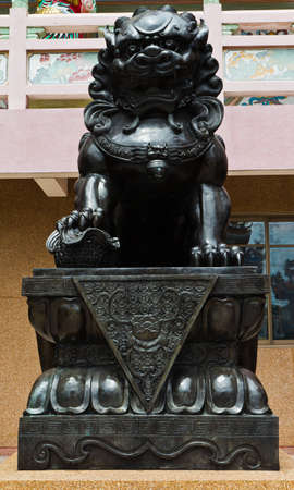 The statues metal lion at the Chinese temple in the daytime.