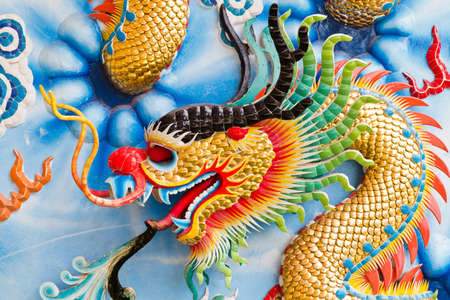 Statue of a dragon on the wall, in a Chinese temple, in the daytime. photo
