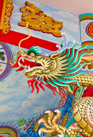 A statue of a dragon on a pole in the Chinese temple in the daytime.