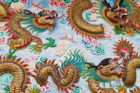 Statue of a dragon on the wall, in a Chinese temple, in the daytime.