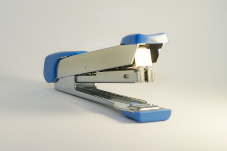 Silver and blue stapler with white background