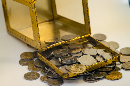 Silver and gold colour of Malaysian coins with white background inside a golden box as the piggy bank