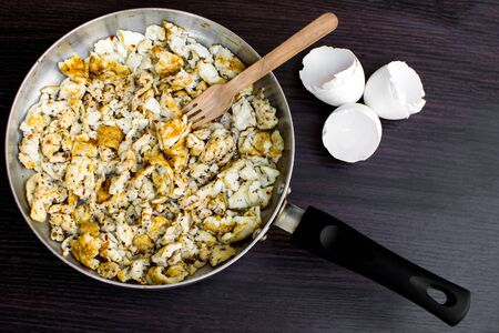 Two whole eggs and five egg whites scrambled in coconut oil in a pan with oregano and chilly flakes to make a protein rich (30 grams) dish