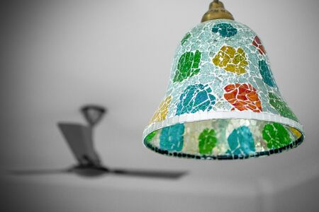 A multicolored lamp-shade dangling from ceiling of room with a fan in the backdrop
